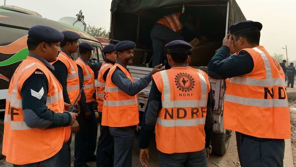 Members of the National Disaster Response Force (NDRF) direct operations near the crash site of a chartered army plane close to the main airport in New Delhi on December 22, 2015. A small chartered aircraft carrying military personnel crashed closed to New Delhi's main airport, killing at least three people on board, Indian rescue officials said. AFP PHOTO/ CHANDAN KHANNA